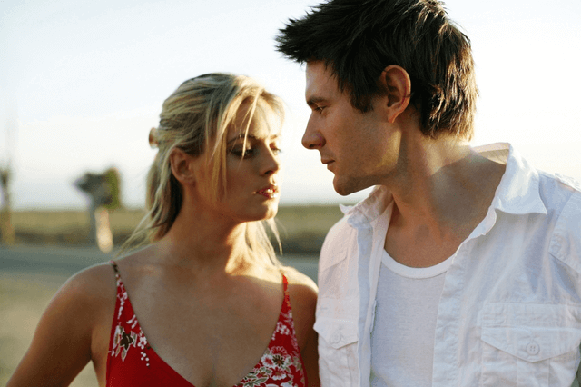 an attractive man and woman looking at each other